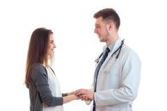 La muchacha linda joven con los soportes largos del pelo enfrente del doctor sostiene su mano y los ` con referencia a la sonrisa Imágenes de archivo libres de regalías