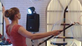 La muchacha linda joven con un palillo con un anillo sopla hacia fuera burbujas de jabón grandes, hace una demostración, primer almacen de metraje de vídeo