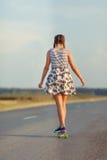 La muchacha linda joven monta el monopatín en el camino Foto de archivo
