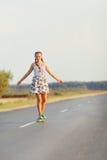 La muchacha linda joven monta el monopatín en el camino Imagen de archivo libre de regalías
