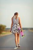La muchacha linda joven monta el monopatín en el camino Fotos de archivo libres de regalías