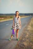 La muchacha linda joven monta el monopatín en el camino Fotografía de archivo