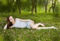 La muchacha linda joven se está inclinando en los gras verdes Fotografía de archivo