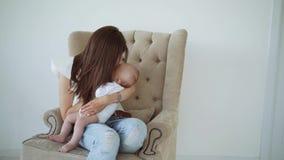 La muchacha linda joven se sienta con el bebé en el asiento metrajes