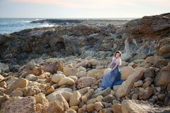 La muchacha linda joven se sienta en dicha en las rocas en medio del mar azul que rabia fotografía de archivo