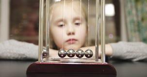 La muchacha linda juega con una cuna del ` s de Newton almacen de video