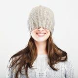 La muchacha linda juguetona del invierno cubre ojos con el sombrero Fotografía de archivo