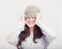 La muchacha linda juguetona del invierno cubre ojos con el sombrero Fotografía de archivo libre de regalías