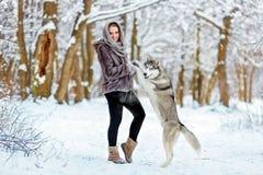 La muchacha linda mantiene su perro de las patas fornido en el fondo de la delantera Imagenes de archivo