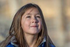 La muchacha linda mira a los skys en un frío, día soleado fotografía de archivo