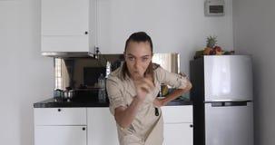 La muchacha linda muestra área de la cocina del gesto del índice almacen de metraje de vídeo