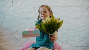 La muchacha linda muestra flores y un regalo y envía besos