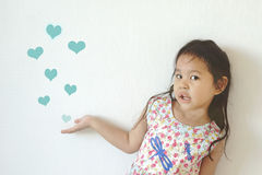 La muchacha linda que muestra muchos dibuja la forma del corazón que sopla en el aire Imágenes de archivo libres de regalías