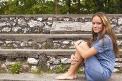 La muchacha linda que se sienta en la piedra camina en el parque histórico Fotos de archivo