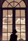 La muchacha linda se coloca cerca de una ventana y mira el cielo con las nubes Foto de archivo
