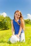 La muchacha linda se sienta en hierba con la bola Foto de archivo