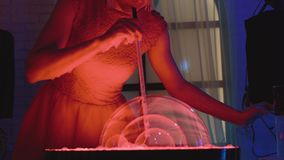 La muchacha linda sopla algunas burbujas de jabón, una en la otra, hace una demostración, primer almacen de metraje de vídeo