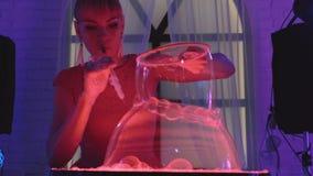 La muchacha linda sopla para arriba dos burbujas de jabón enormes y los juegos con ellos, hacen una demostración, primer almacen de video