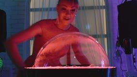 La muchacha linda sopla para arriba una burbuja grande en el soporte y los juegos con él, hacen una demostración, primer metrajes