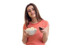 La muchacha linda sostiene el cuenco de palomitas de maíz y de canales teledirigidos del interruptor Imagen de archivo