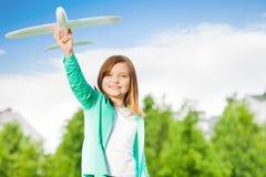 La muchacha linda sostiene el juguete del aeroplano con el brazo recto Foto de archivo libre de regalías