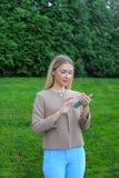 La muchacha linda sostiene el teléfono móvil y lo utiliza, sonríe y expresa e imagen de archivo