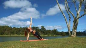 La muchacha lleva a cabo actitud de la yoga con el brazo y la pierna en el banco del lago