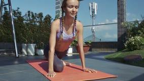La muchacha lleva a cabo actitud de la yoga con los ojos cerrados en terraza