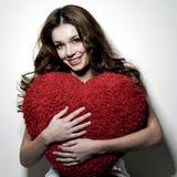La muchacha lleva a cabo el corazón de la felpa Imágenes de archivo libres de regalías