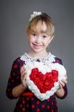 La muchacha lleva a cabo el corazón disponible y sonríe Fotografía de archivo libre de regalías