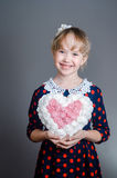 La muchacha lleva a cabo el corazón disponible y sonríe Imagen de archivo libre de regalías