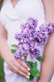 La muchacha lleva a cabo n sus manos una rama de lilas florecientes fotos de archivo libres de regalías