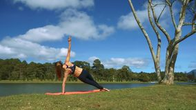 La muchacha lleva a cabo la posición de la yoga contra paisaje del río