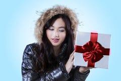 La muchacha lleva a cabo presentes con el arco rojo Fotos de archivo libres de regalías