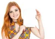 La muchacha lleva a cabo rectángulo en blanco y mira la cámara Soldado enrollado en el ejército Redheaded Foto de archivo libre de regalías