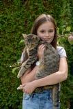 La muchacha lleva el gato Fotos de archivo