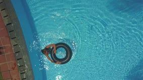 La muchacha lleva salvavidas la piscina para nadar y para relajarse bajo rayos del sol metrajes