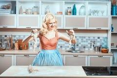 La muchacha llora en la cocina, sus manos pegadas a la pasta Foto de archivo