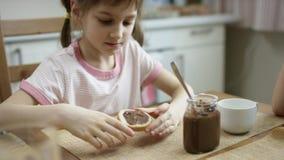 La muchacha mancha la goma del chocolate en un pedazo de pan después de que la cena entonces lo coma metrajes