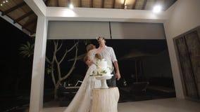 La muchacha mancha un pedazo de pastel de bodas en la cara del novio La celebración de la boda metrajes