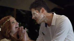 La muchacha mancha un pedazo de pastel de bodas en la cara del novio La celebración de la boda almacen de metraje de vídeo