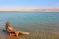 La muchacha manchada con fango terapéutico toma el sol, mar muerto Imagen de archivo