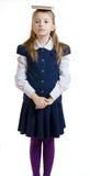 La muchacha mantiene el libro en la cabeza un uniforme escolar Imagen de archivo libre de regalías