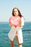 la muchacha mantiene la bola de aire corazón de la forma Foto de archivo