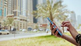 La muchacha marca un número o un mensaje en el smartphone contra el contexto de las calles de la ciudad de Dubai Da el primer almacen de video