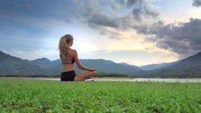 La muchacha medita en la actitud Lotus de la yoga en el banco del lago debajo del cielo nublado