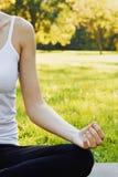 La muchacha medita mientras que practica yoga al aire libre en parque fotos de archivo