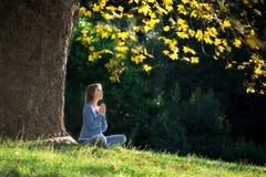 La muchacha medita sentarse en la hierba debajo de árbol de arce en otoño Fotografía de archivo