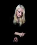 La muchacha melancólica en un fondo negro. Imagen de archivo libre de regalías