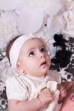 La muchacha 6 meses de vestido blanco mira para arriba en sorpresa Foto de archivo